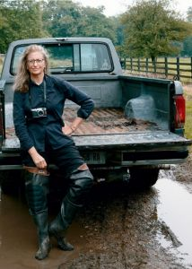 Annie Leibovitz sitting on the back of a pick up truck