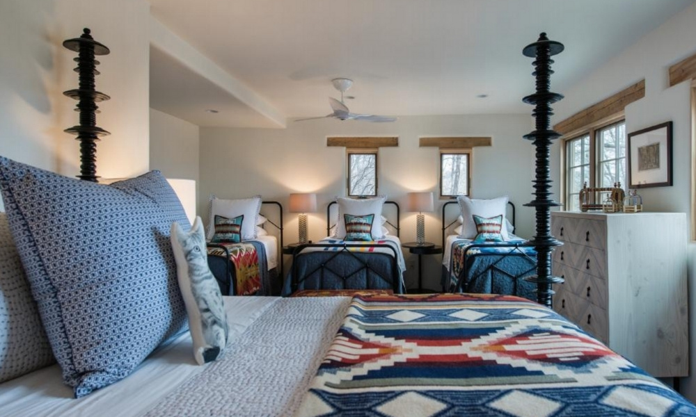A cozy guest room with three twin beds and a queen