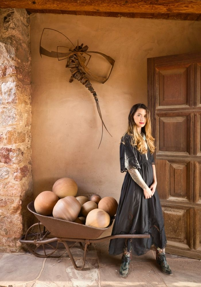 A woman stands in front of sculpture against an adobe wall.