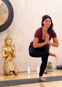 A woman holding a standing figure four yoga pose.