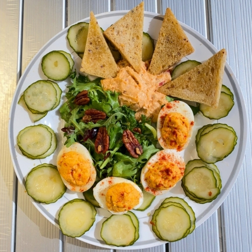 A plate of deviled eggs, hummus and pickles.