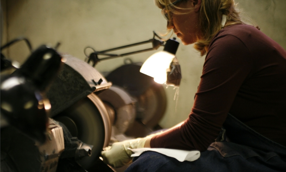 A woman at work at the grinding wheel.
